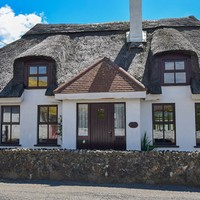 Stroll to the beach from this €275k thatched-roof home in Wexford
