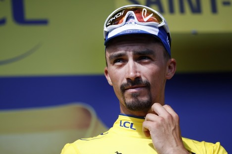 France's Julian Alaphilippe wears the overall leader's yellow jersey on the podium.