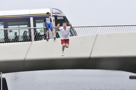 Lee Byrne with local children from Dublin as they jump off Mayor Street Bridge in the Royal Canal in Dublin earlier today.