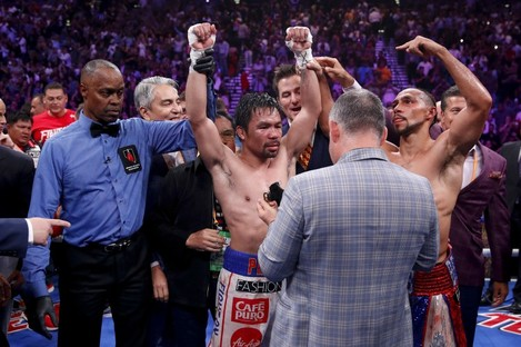 Referee Kenny Bayless holds up Pacquiao's hand as he is declared the winner by split decision.