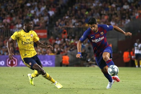 Barcelona's Luis Suarez, right, vies for the ball with Arsenal's Ainsley Maitland-Niles.