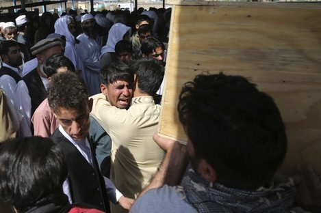 Relatives grieve near the near the coffins of victims of the Dubai City wedding hall.
