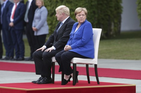 German Chancellor Angela Merkel welcomes Britain's Prime Minister Boris Johnson with military honors for a meeting at the Chancellery in Berlin.