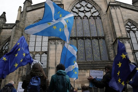 Protesters holding Scottish and European flags gather in front of St Gilles Cathedral facing the Scottish Court of Session in Edinburgh, Scotland on Wednesday