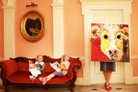 Irish artist Deborah Donnelly holds one of her paintings while watched by her children during the launch of a new series of books aimed at painting enthusiasts.