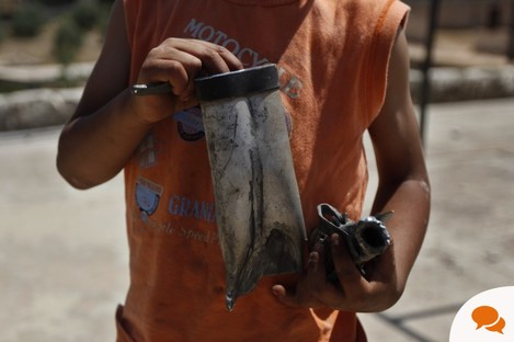 A young boy holds the remains of a rocket he said hit his family's home in Idlib, Syria, on Thursday