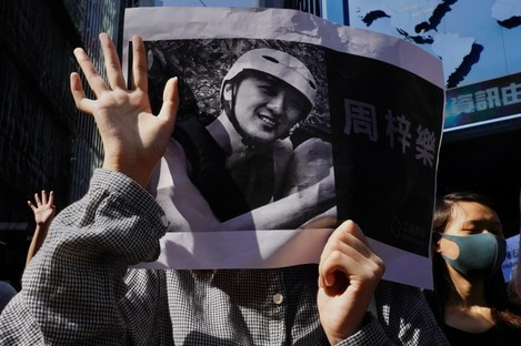 Protesters hold a photo of Alex Chow who died
