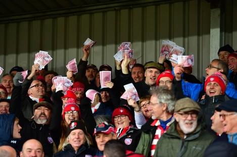 Gloucester fans waving fake money.