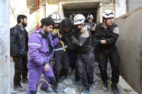 Photo released in February 2019 showing Syrian White Helmet members carrying an injured man from a building in Idlib hit by a shell from Syrian forces.