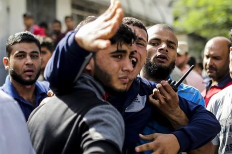 Palestinian men mourn outside the al-Shifa hospital in Gaza city.