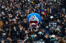 Tens of thousands march in Hong Kong pro-democracy rally after police use tear gas in clashes