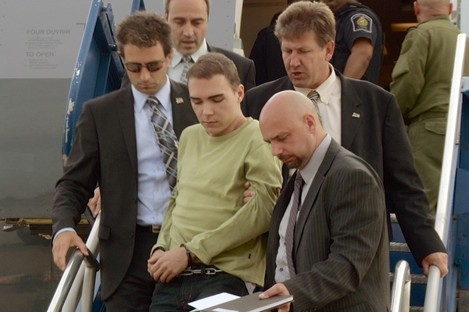 Luka Rocco Magnotta is taken by police from a Canadian military plane to a waiting van in Quebec on Monday
