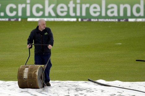A groundsman attempts to clear the water at Storment.