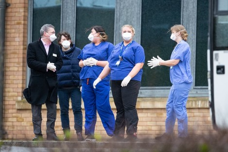 Members of staff wait as coaches carrying Coronavirus evacuees arrive at Kents Hill Park Training and Conference Centre, in Milton Keynes, after being repatriated to the UK from the coronavirus-hit city of Wuhan in China.