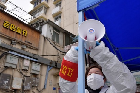 A government staff member adjusts a loudspeaker in Wuhan.