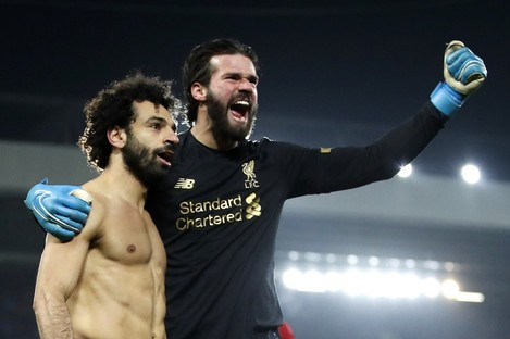 Mo Salah and Alisson Becker celebrate Liverpool's January win at home to Manchester United.