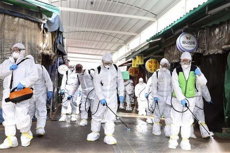 Workers wearing protective suits spraying disinfectant in Seoul, South Korea.