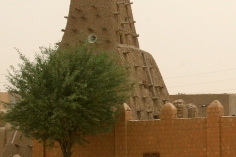 a man walks past the Sankore Mosque, a UNESCO World Heritage Site, in Timbuktu, Mal