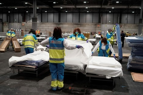 Health personnel prepare beds at the field hospital set up at the IFEMA Exhibition center in Madrid.