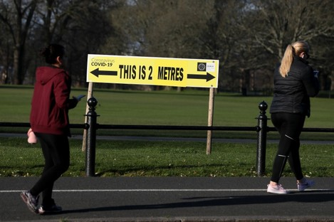 People walk past a sign encouraging social distancing in Dublin's Phoenix Park