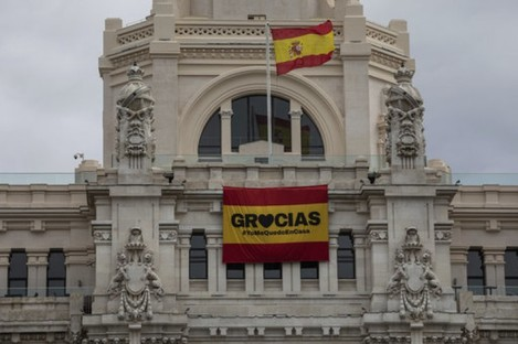 """A sign that reads: """"Thank you #IstayAtHome"""" hangs on the front of the Madrid city hall."""