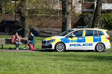 Police stop to move on two women on Primrose Hill, London, as the UK continues in lockdown