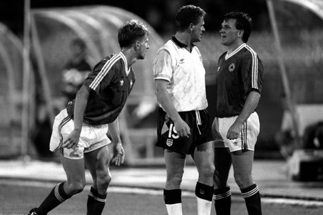 Ray Houghton and Paul Gascoigne square up at Italia '90, with Chris Morris watching on.