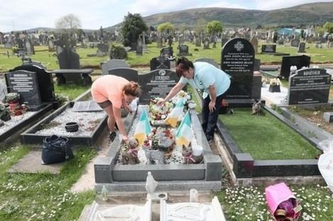 Two women water plants at Milltown Cemetery in Belfast.