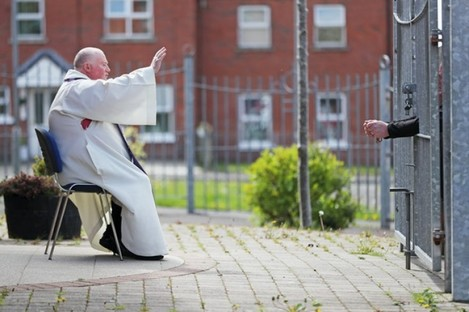 Fr McCafferty hearing confessions while observing social distancing though the locked gates of Corpus Christi Church
