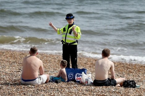 A police officer advises people to leave the beach in Brighton.