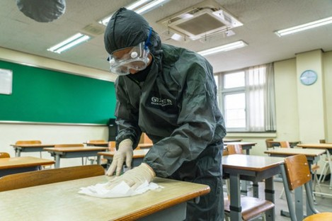 A worker wearing protective gear cleans desks as South Korea prepares to reopen schools.