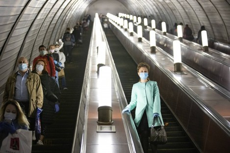 People wearing face masks and gloves on an escalator today in Moscow, Russia.