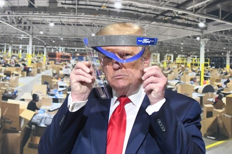 Donald Trump looks through a face shield at the Ford factory in Michigan