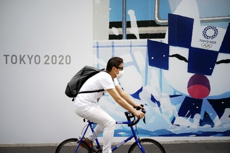 A man in Tokyo last week riding a bicycle in front of an advertisement of Tokyo 2020 Olympic Games.