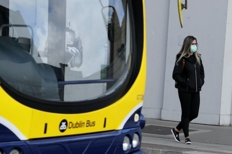 A woman wearing a protective face mask waits at a bus stop in Dublin's city centre.