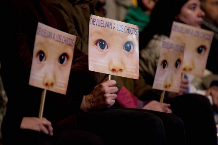 """People hold signs that read in Spanish """"Give the children back"""" outside the Buenos Aires court yesterday."""
