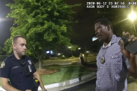 This screen grab taken from body camera video provided by the Atlanta Police Department shows Rayshard Brooks speaking with Officer Garrett Rolfe in the car park