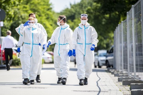 Soldiers in protective suits and wearing mouth-and-nose masks go to the homes to test more people for the coronavirus.