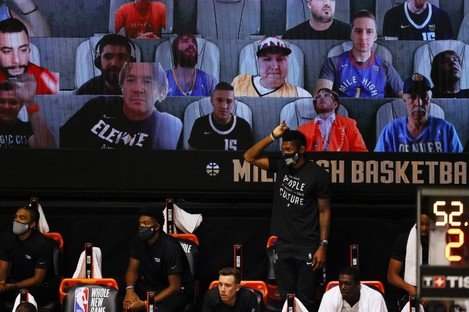 Members of the Miami Heat bench react with virtual fans in the background this weekend.