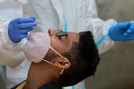 A healthcare worker collects a swab sample from a man in New Delhi, India.