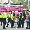 Climate activists glue themselves to the ground in London and block road around Parliament