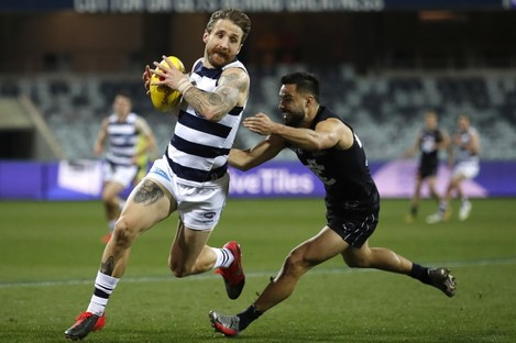 Zach Tuohy of the Cats is tackled by Michael Gibbons of the Blues.