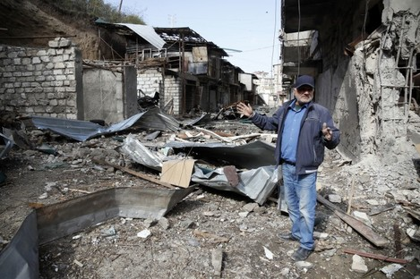 Eduard Chechyan gestures in the yard of his apartment building, destroyed by shelling by Azerbaijan's artillery