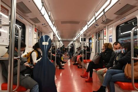 People wearing face masks take a subway in Milan.