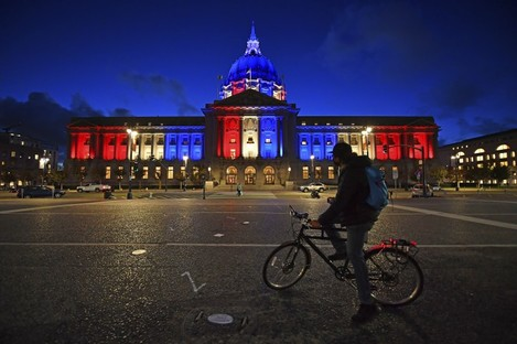 A bicyclist stops to look at the red, white and blue lights illuminating San Francisco City Hall