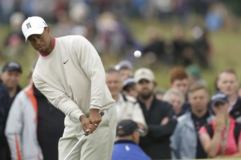 Tiger Woods chip towards the pin on the fifth hole.