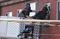 Booby-trapped: bomb squad to try and enter suspect shooter's apartment