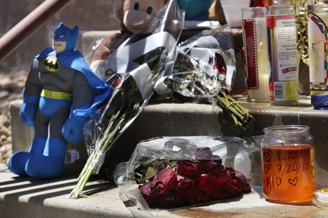 Candles, flowers, and a Batman figure are shown at a memorial.