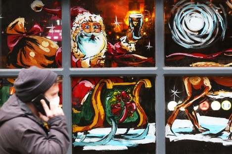 A man walks by a Christmas display in the windows of the Hairy Lemon pub in Dublin city.
