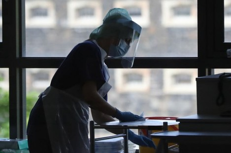 A hospital worker cleans a surface (file photo)